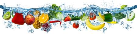 Varias frutas y verduras frescas salpicando en agua azul clara splash concepto de frescura de dieta de alimentos saludables aislado sobre fondo blanco.