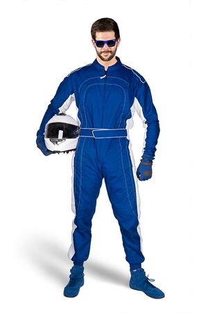 Race driver in blue white motorsport overall shoes gloves and safety gear crash helmet under his arm determined and ready to go isolated on white background. Car racing motorcycle sport concept. Stockfoto