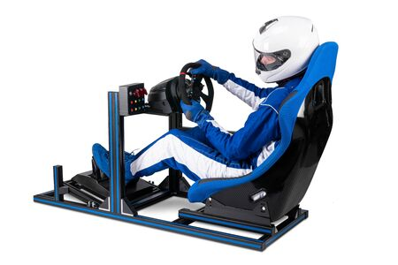 race driver in blue overall with helmet taining on simracing aluminum simulator rig for video game racing. Motorsport car bucket seat steering wheel pedals isolated on white background Stockfoto