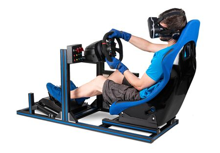 gamer in blue tshirt with VR virtual reality glasses training on simracing aluminum simulator rig for video game racing. Motorsport car bucket seat steering wheel pedals isolated on white background Stockfoto