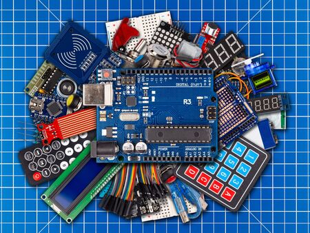 collage of microcontroller board display sensor button switches cable wire accessories and equipment on blue cutting matte workplace electronics concept background