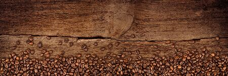fresh roasted coffee beans on natural dark oak wood panorama wide plank wooden closeup macro background
