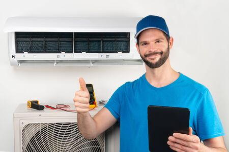 Installation service fix  repair maintenance of an air conditioner indoor unit, by cryogenist technican worker giving thumbs up ready to go after commissioning in blue shirt and baseball cap