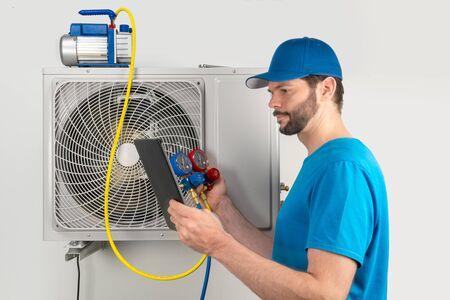 Installatieservice fix reparatie onderhoud van een airconditioner buitenunit, door cryogenist technican werknemer evacueer het systeem met vacuümpomp en spruitstukmeters tablet in blauw shirt en baseballcap Stockfoto