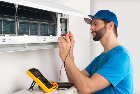 Installation service fix  repair maintenance of an air conditioner indoor unit, by cryogenist technican worker with multimeter checking electric blue shirt and baseball cap Stockfoto