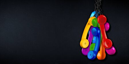bunch of colorful rainbow colored old fashioned retro phone reciever with black telephone wire on black slate copy space blackboard background, business communication support service concept