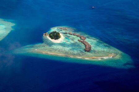 aerial view of tropical paradise maldives island resort with coral reef and turquoise blue ocean tourism background