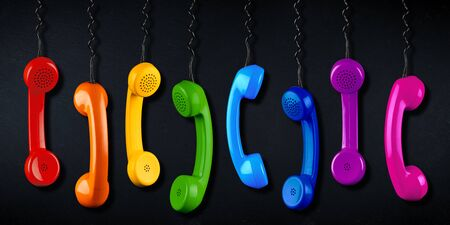 row of colorful rainbow colored old fashioned retro phone reciever with black telephone wire on black slate blackboard background, business communication support service concept