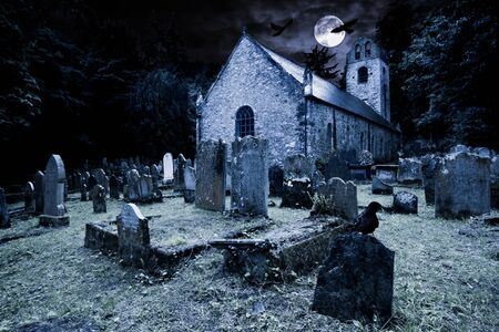 old graveyard with ancient tombstones grave stone and old church in front of full moon black raven dark night spooky horror background
