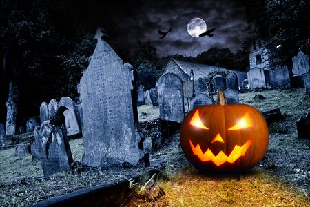 glowing orange halloween pumpkin on old graveyard in front of full moon black raven church dark night spooky horror background