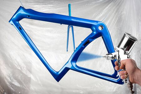 hand of painter with spray gun producing a shiny new fresh paintwork coating paint of a metallic blue carbon racing road bicycle and fork in front of paint booth. cycling manufacturing production background Stockfoto