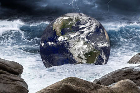 planet earth globe in thunderstorm wave of water in the rough ocean. Climate change global warming concept on sea background.