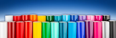 Row of various rainbow colored vinyl car wrapping or plotter cutting sticker foil film rolls on blue white wide panorama banner background