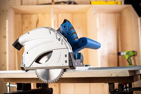 hand circular saw with piece of wood on workbench. closeup of sawing machine woodworking construction tool concept furniture making diy background