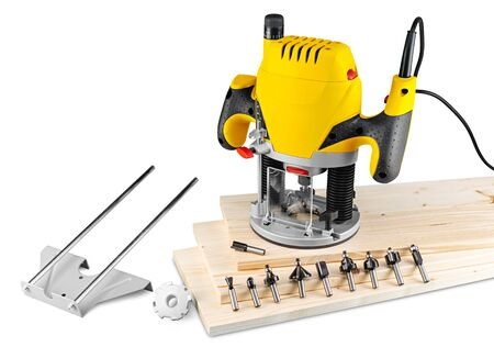 yellow wood router machine with cutter bits guide and copy ring on wooden spruce planks isolated on white background. carpentry construction diy concept.