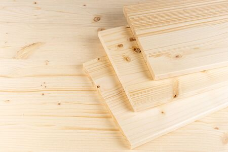 stack of spruce wood construction planks or boards on wooden background. Natural material carpentry diy industry furniture making concept. Standard-Bild