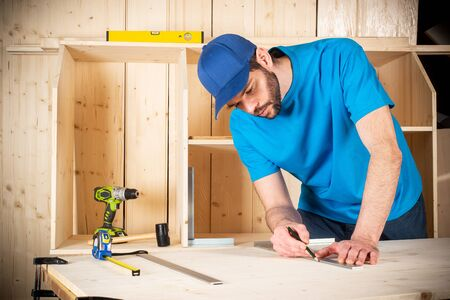 young male carpenter with beard pencil and stop angle meter at work. measuring on wood plank  woodworking construction tool concept furniture making diy background