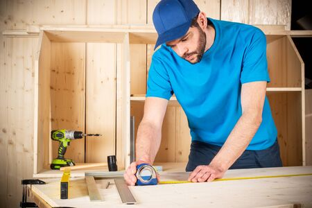 young male carpenter with beard and metal tape measure at work. measuring on wood plank  woodworking construction tool concept furniture making diy background