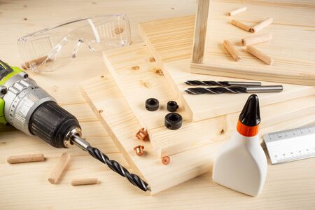 wooden dowel joint pins drill glue wood planks safety glasses cordless screwdriver and tools on spruce background. Carpenter industry funiture making concept. Standard-Bild