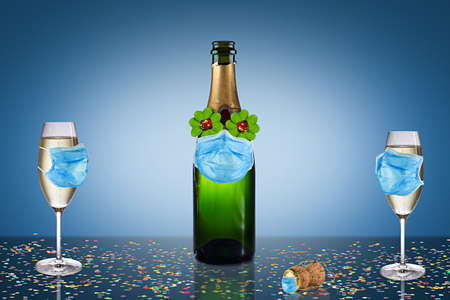 happy new year eve covid-19 coronavirus social distancing party concept. champagne bottle glass with pandemic breathing mask on blue white confetti background