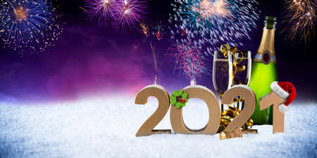 happy new year eve 2021 number colorful fireworks with santa hat four leaf clover champagne bottle glass on snow front of red purple blue black bokeh night panorama background Standard-Bild