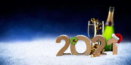 happy new year 2021 number with santa hat four leaf clover champagne bottle glass on snow front of blue black bokeh night panorama background Standard-Bild