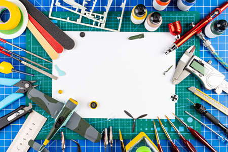 desktop view from above of assembly painting of retro scale model plane concept copy space background. modeling tools airbrush gun paint kit parts blue green cutting mat knife and brush on work desk Standard-Bild