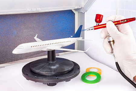 paint job with red metal airbrush spray paint gun on red scale model on modern white blue passenger airplane plane in paint booth. hobby industry concept background