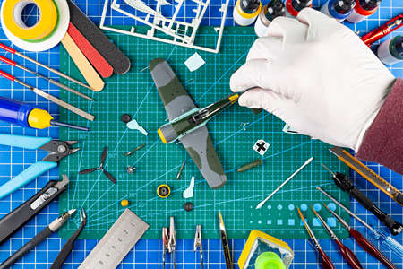desktop view from above of assembly and painting of retro scale model fighter plane concept background. modeling tools airbrush gun paint kit parts blue green cutting mat knife and brush on work desk Standard-Bild