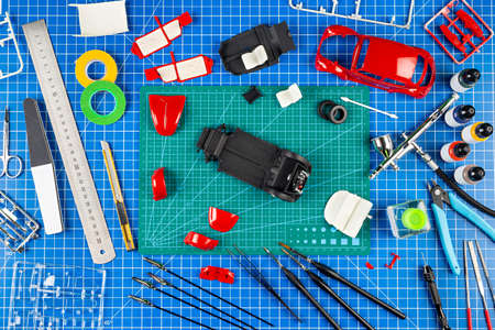 desktop view from above of assembly and painting of a red retro scale model car vehicle concept background. modeling tools airbrush gun paint kit parts blue green cutting mat knife and brush on work desk
