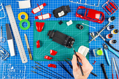assembly and painting of a red retro scale model car vehicle concept background. modeling tools airbrush gun paint kit parts blue green cutting mat knife and brush on work desk view from above.
