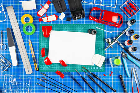assembly and painting of a red retro scale model car vehicle concept copy space background. modeling tools airbrush gun paint kit parts blue green cutting mat knife and brush work desk view