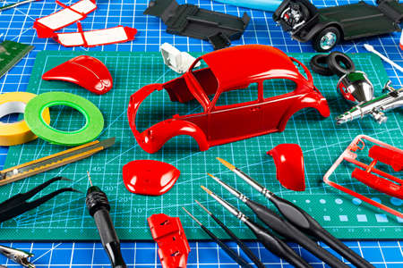 desktop view assembly and painting of a red retro scale model car vehicle concept background. modeling tools airbrush gun paint kit parts blue green cutting mat knife and brush on work desk Standard-Bild