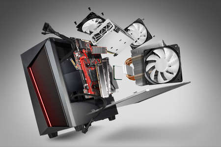 exploded view of a modern computer. hardware components mainboard cpu processor graphic card RAM cables and cooling fan flying out of black red PC case on gray abstract technology concept background