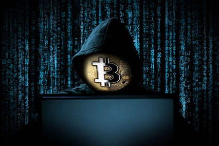 hacker with bitcoin face mask behind notebook laptop in front of blue source binary code background internet cyber hack attack crypto currency blockchain computer concept Standard-Bild