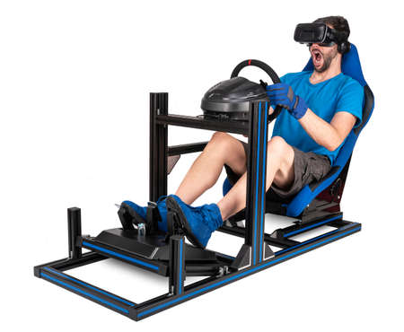 gamer in blue tshirt VR virtual reality glasses enjoys immersion with open mouth on simracing aluminum simulator rig for video game racing. Motorsport sim racing concept isolated on white background Foto de archivo