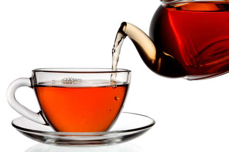 Tea being poured into glass tea cup isolated on a white background.  photo