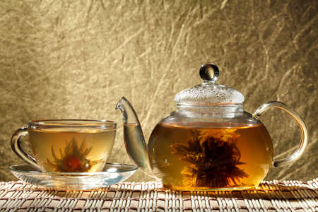 Glass teapot and a cup of green tea on a gold background photo