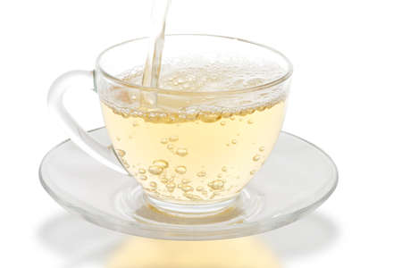 green tea pouring into glass cup photo