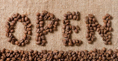 The word Open from coffee beans on linea material  photo