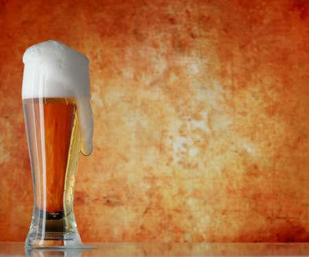 brew beer: Vaso de cerveza con espuma sobre fondo amarillo  Foto de archivo