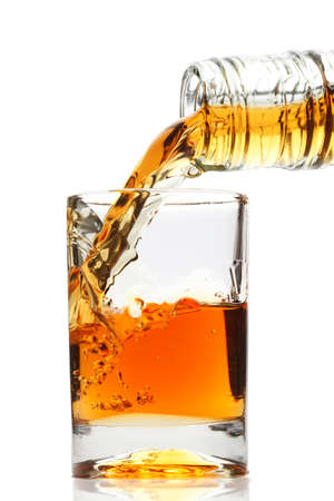 whiskey being poured into a glass Imagens