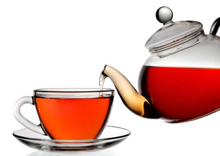 tea pot: Tea being poured into glass tea cup isolated on a white background.