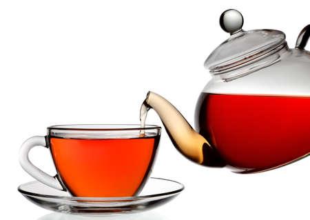 Thee wordt gegoten in glas thee kopje geïsoleerd op een witte achtergrond. Stockfoto