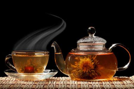teepflanze: Glas Teekanne und eine Tasse gr�nen Tee auf einem schwarzen Hintergrund