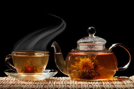 Glass teapot and a cup of green tea on a black background photo