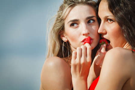 Two sexy girls with strawberries