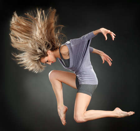 acrobat gymnast: attractive jumping woman dancer