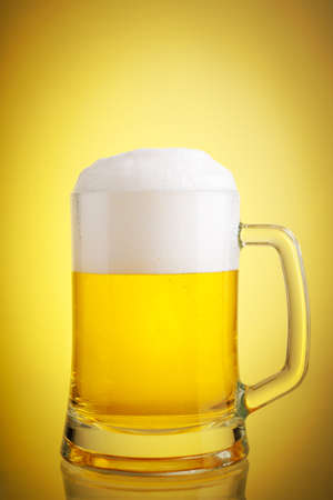 Glass of beer close-up with froth over yellow background photo