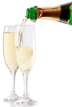 Champagne is poured into two glasses photo